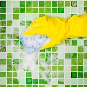 Person wearing rubber gloves scrubbing the tile with a sponge