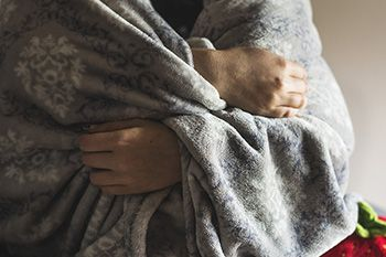 Person wearing a blanket over their shoulders