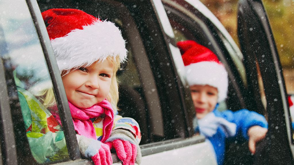 Two children sticking their heads outside of a car window wearing Santa hats