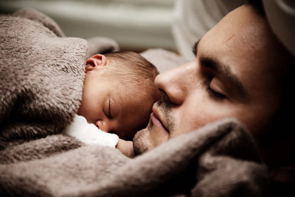 Man sleeping with a baby laying on his chest