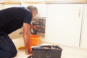 Person doing maintenance under a sink