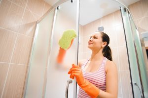 Woman cleaning the glass on her shower walls
