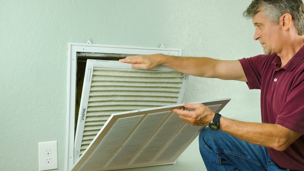 Person inspecting a ventilation system