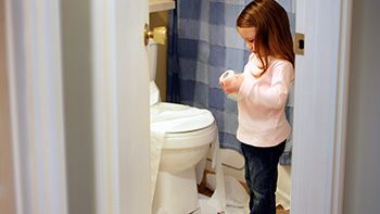 child standing next to a toilet holding a roll of toilet paper